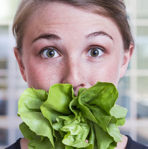Young-woman-with-mouth-stuffed-with-salad-lettuce